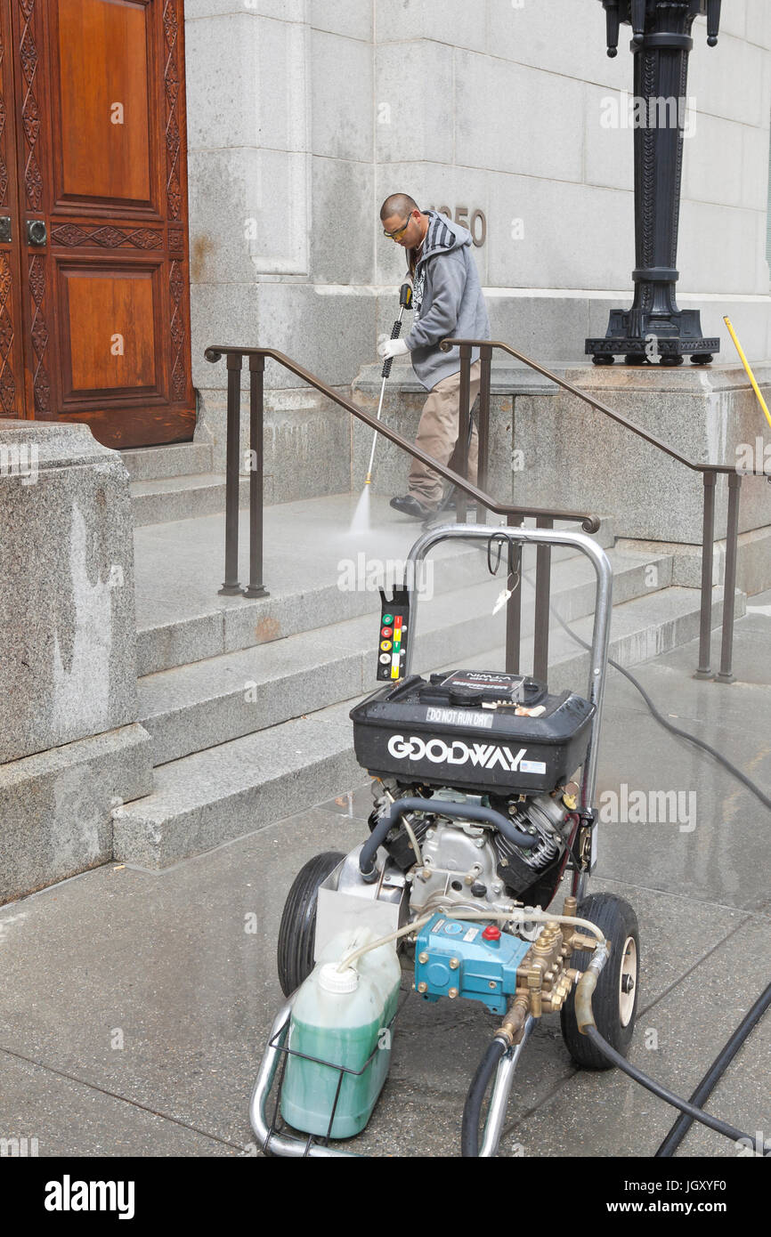 Building maintenance man cleaning building entrance with