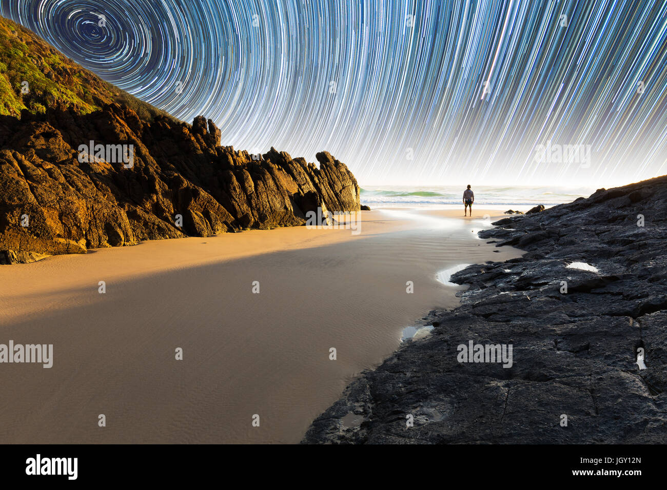 A man standing on a beautiful, isolated beach in Australia underneath a mesmerizing star trail - Stock Image