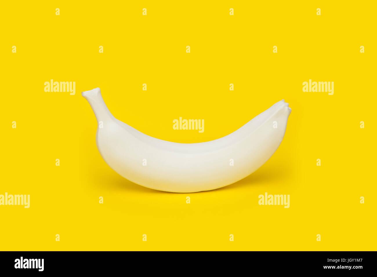 Banana painted white on yellow background - Stock Image