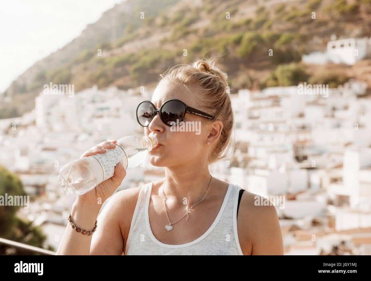 Woman drinking water on viewing platform overlooking town, Mijas Pueblo, Andalucia, Spain - Stock Image
