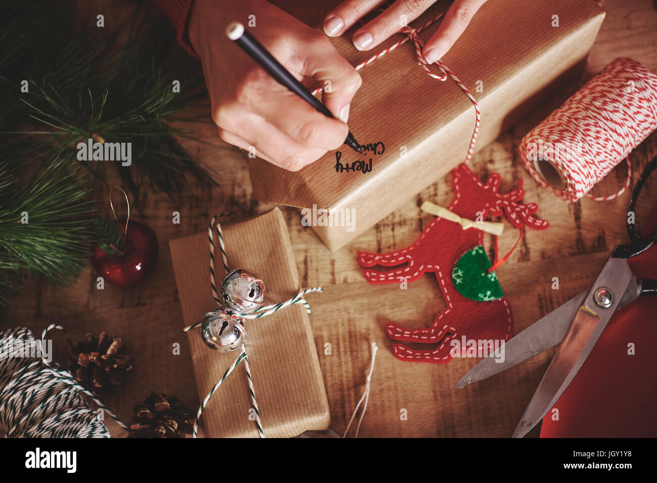 Woman labelling christmas gift - Stock Image