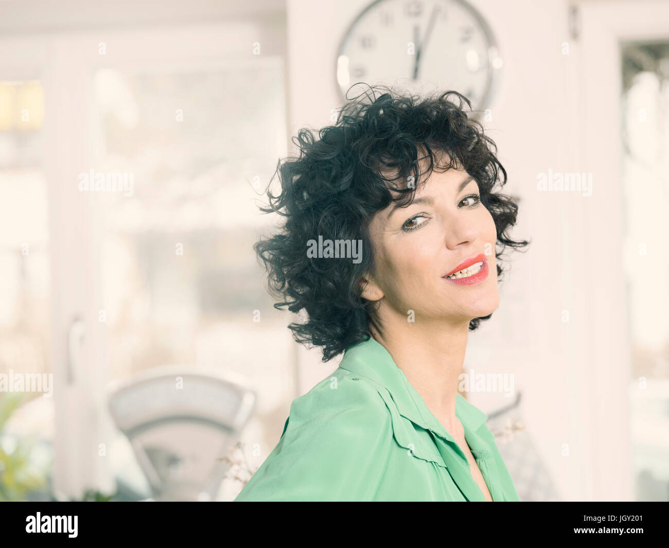 Portrait of curly haired woman looking at camera smiling - Stock Image