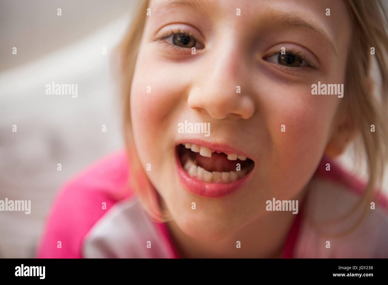 Portrait of girl with missing tooth looking at camera mouth open - Stock Image