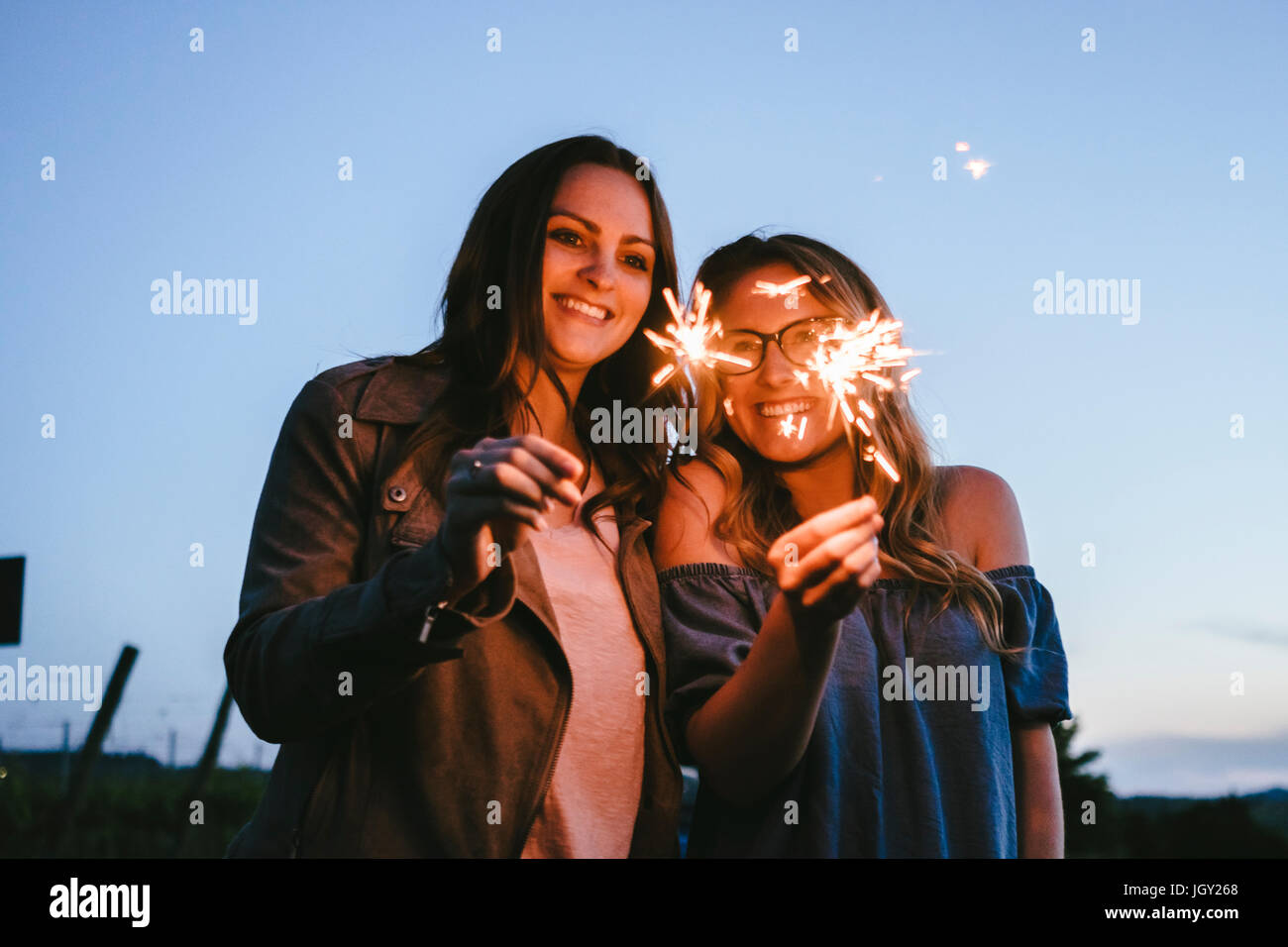 Friends playing with sparklers - Stock Image