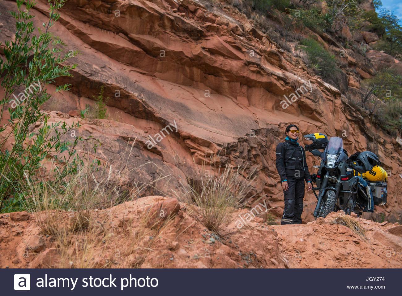 Woman standing next to touring motorbike, Potosi, Bolivia - Stock Image