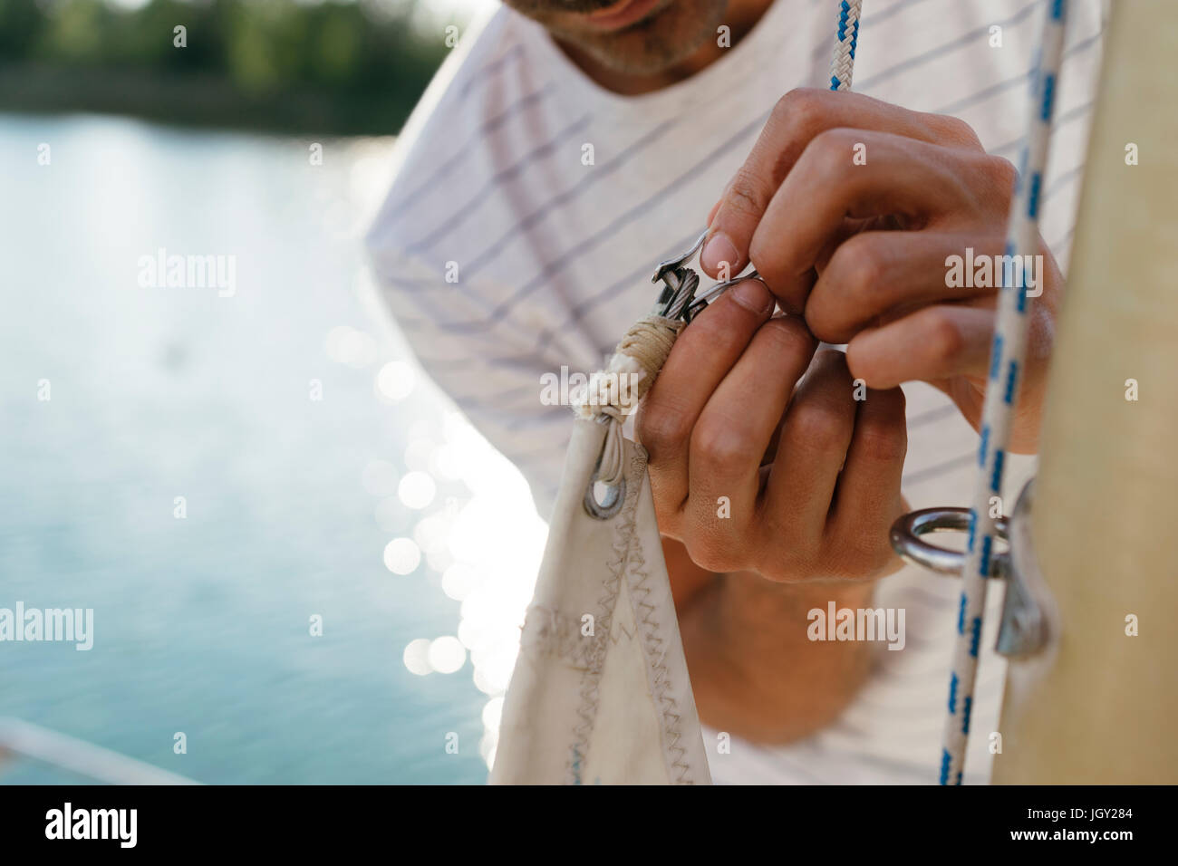 Man on sailing boat, attaching sail to mast, close-up - Stock Image