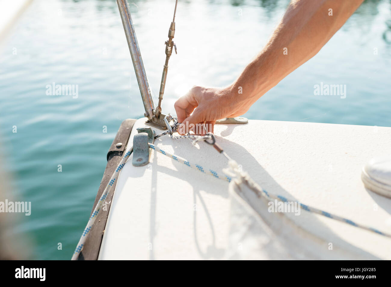 Man on sailing boat, fastening sail, close-up - Stock Image