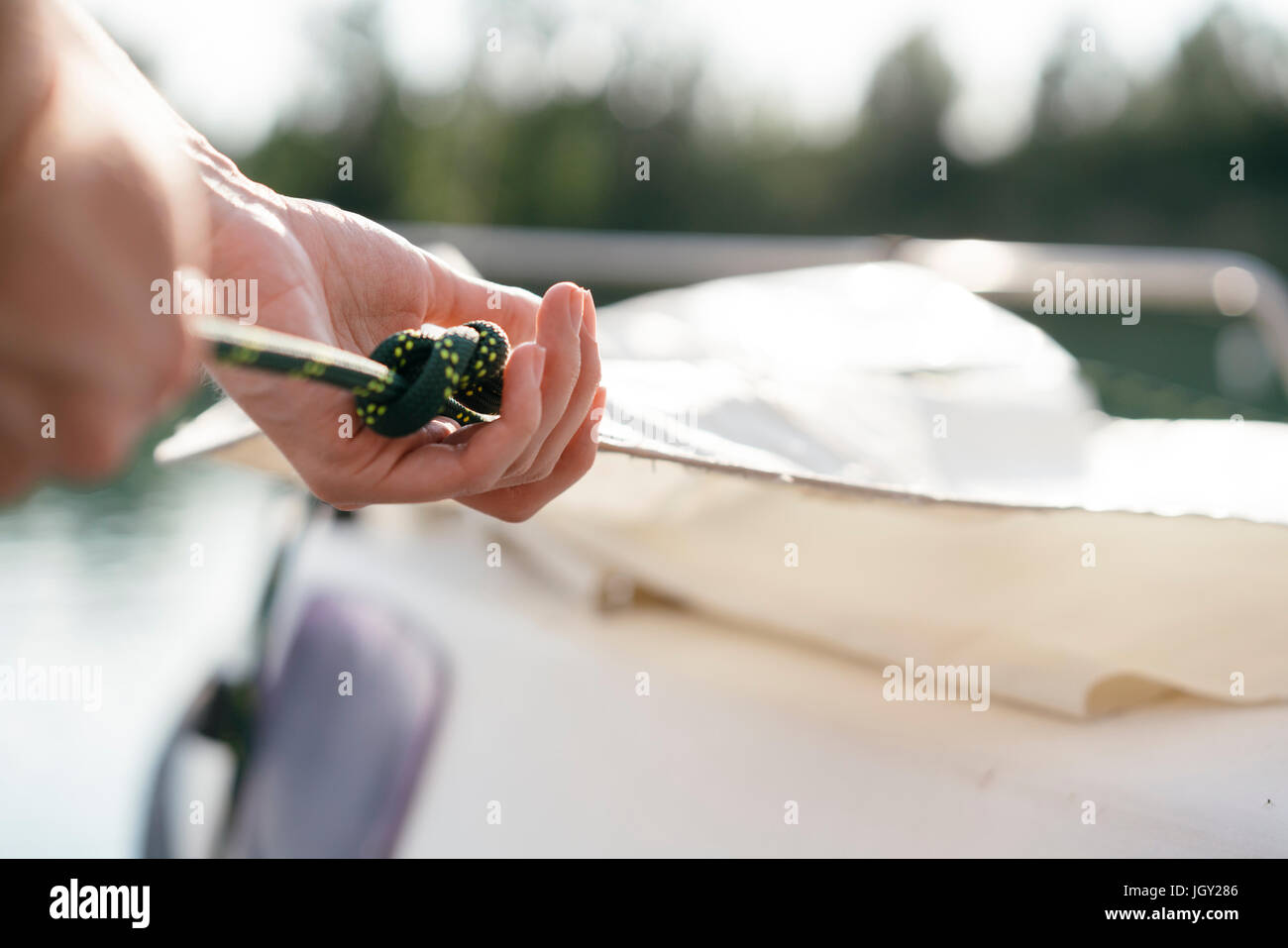 Man on sailing boat, hoisting sail, close-up - Stock Image