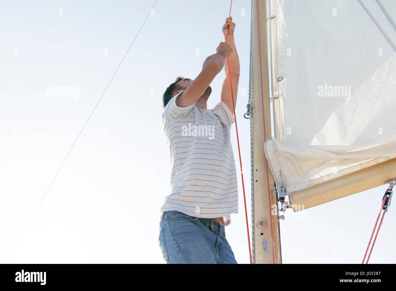 Man on sailing boat, hoisting sail - Stock Image
