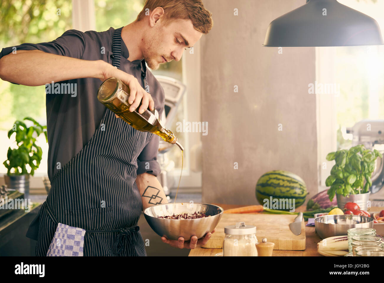 Chef drizzling oil on bowl of food - Stock Image