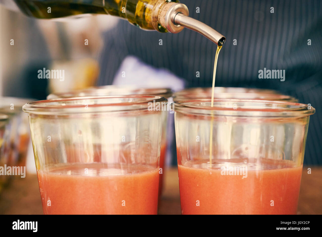 Cropped view of olive oil being drizzled into smoothie - Stock Image
