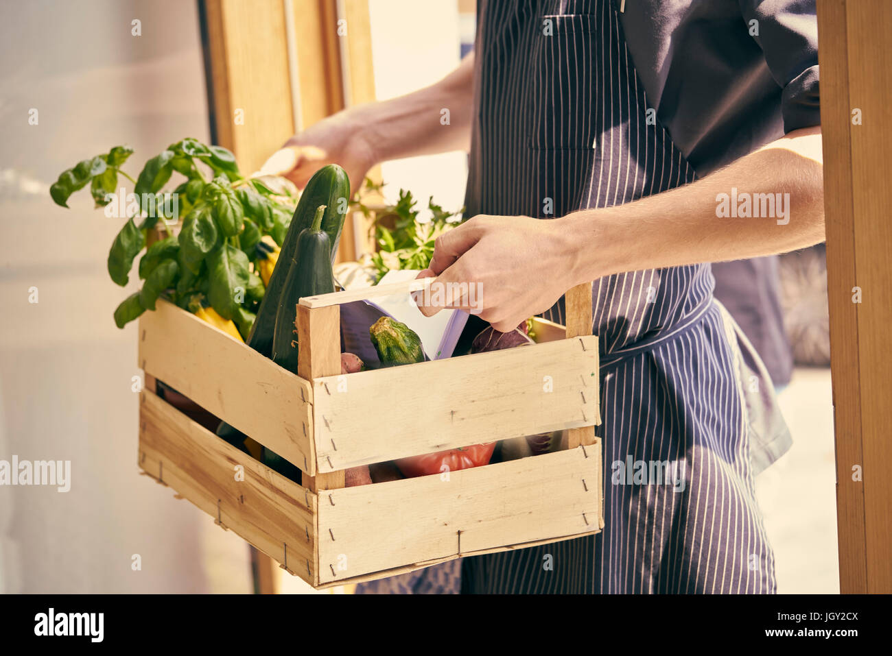 Cropped view of chef carrying crate of vegetables - Stock Image