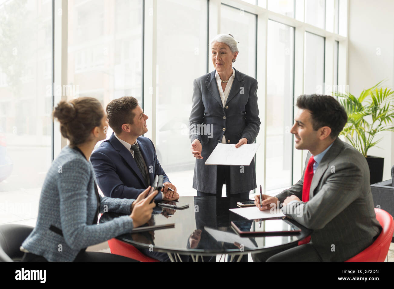 Businesswoman explaining to business team in boardroom meeting - Stock Image