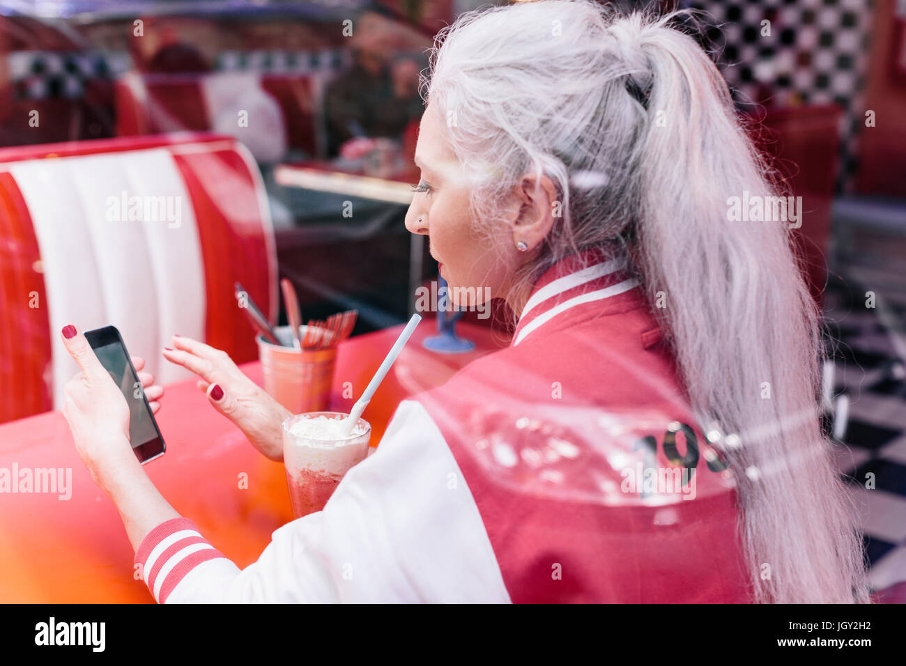 Mature woman in baseball jacket looking at smartphone in 1950's diner - Stock Image