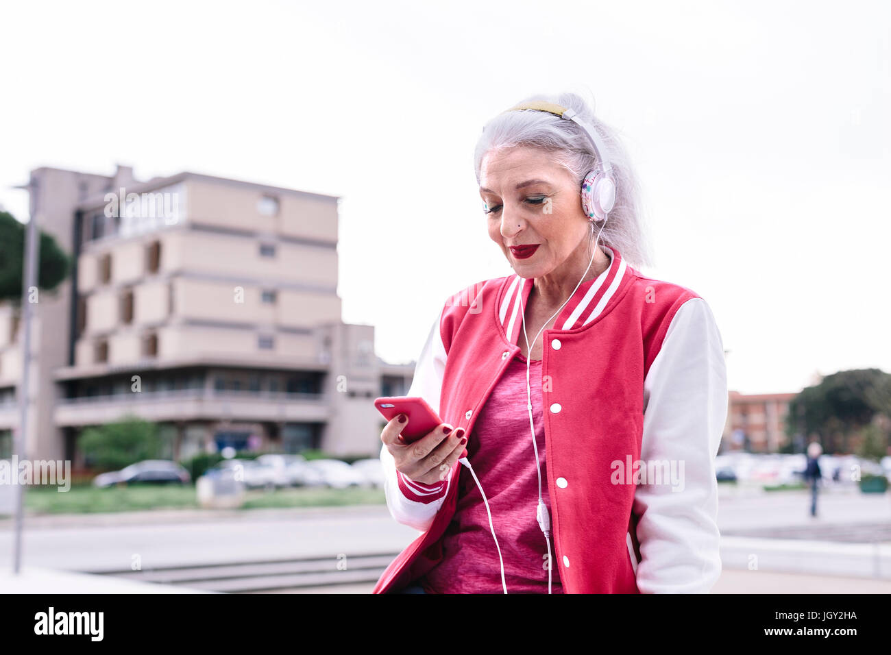 Mature woman in baseball jacket listening to headphones and looking at smartphone - Stock Image