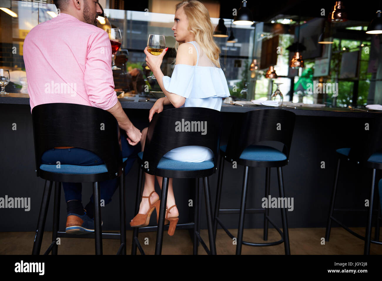 Rear view of man touching angry young woman's knee at bar - Stock Image