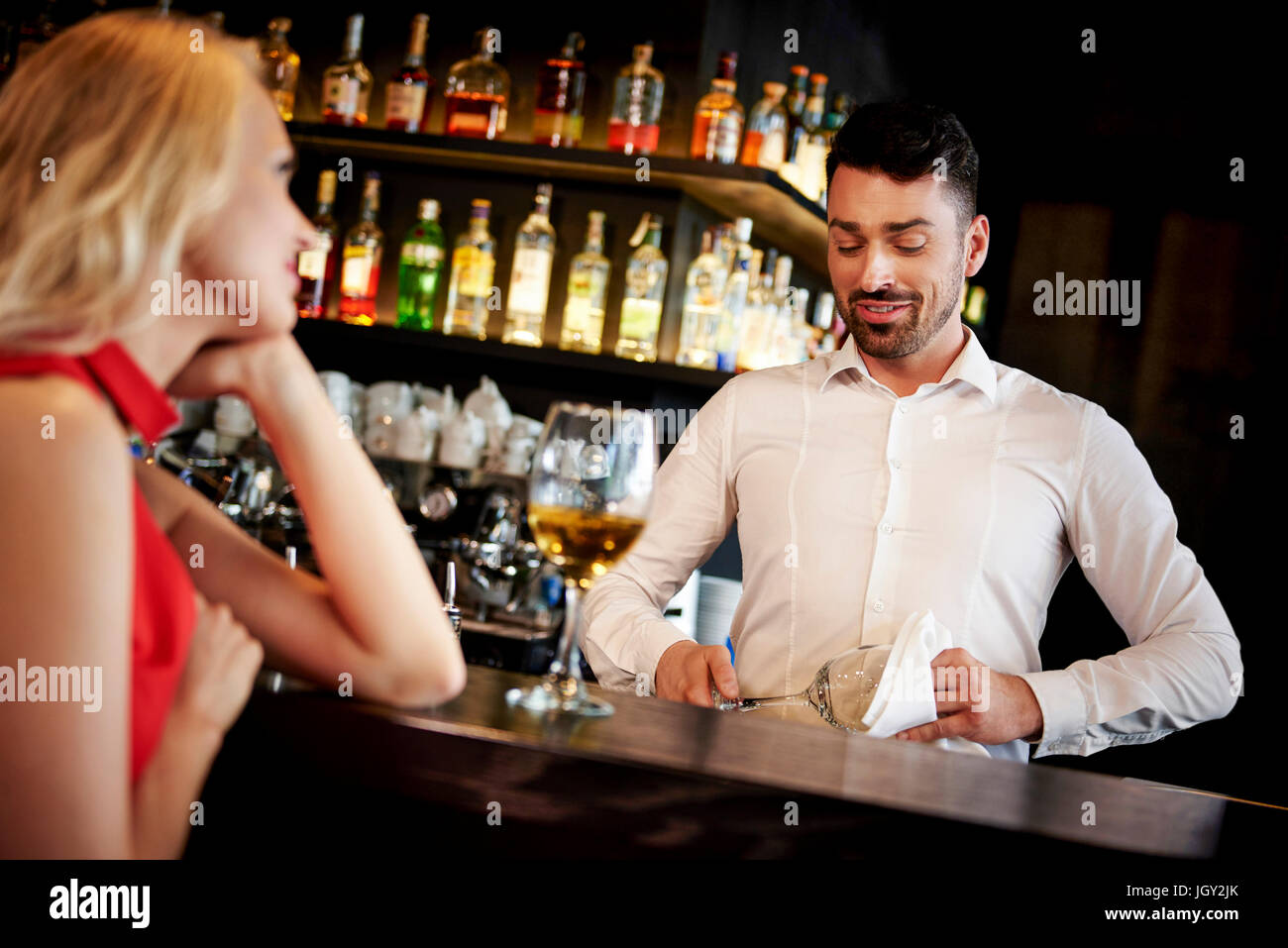 Barman flirting with young woman sitting at bar - Stock Image
