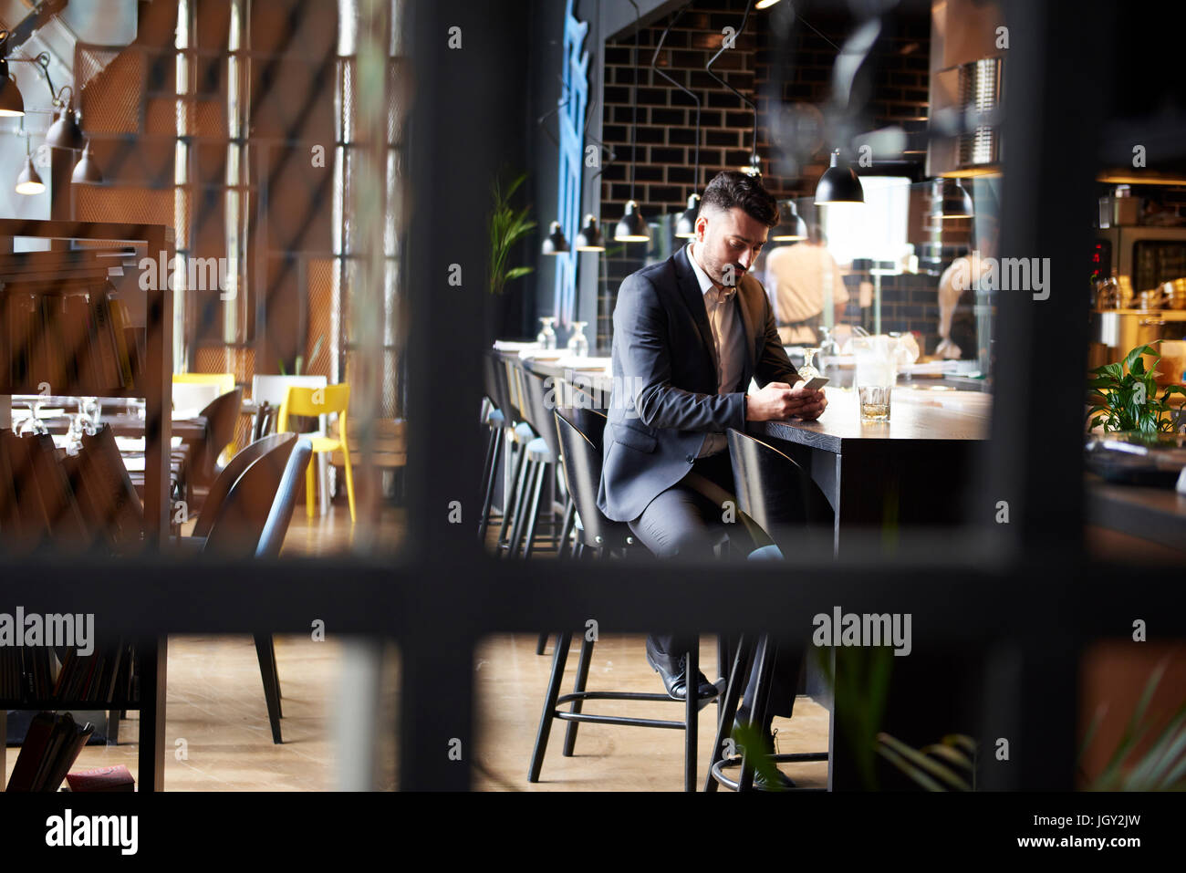Disappointed man looking at smartphone while sitting at bar - Stock Image