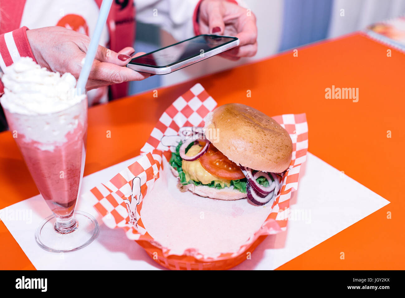 Cropped shot of woman's hands looking at smartphone in 1950's diner - Stock Image