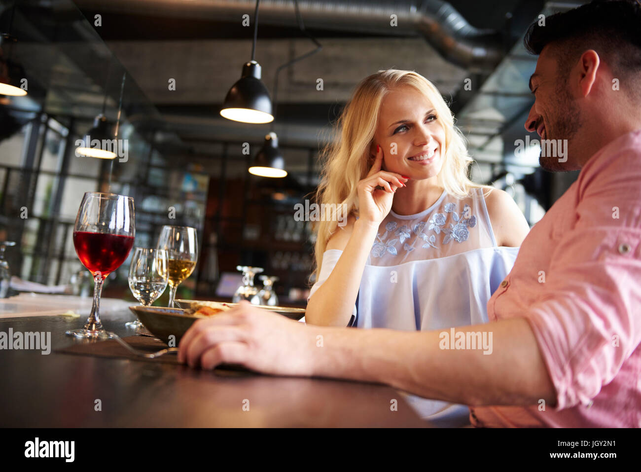 Couple chatting at restaurant table - Stock Image