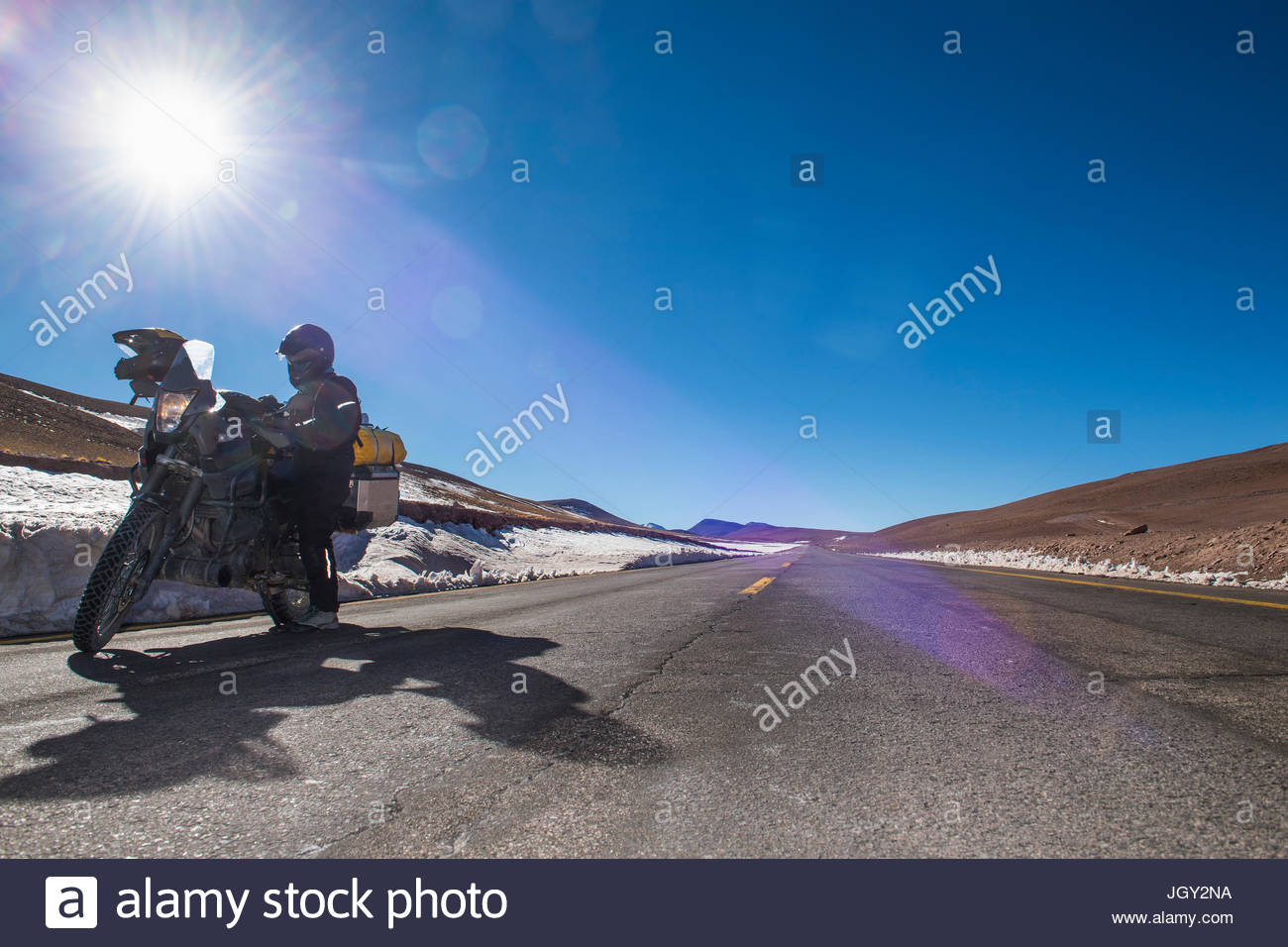 Woman beside motorbike, parked at side of road, Reserva Nacional Los Flamencos national park, Antofagasta, Chile, - Stock Image