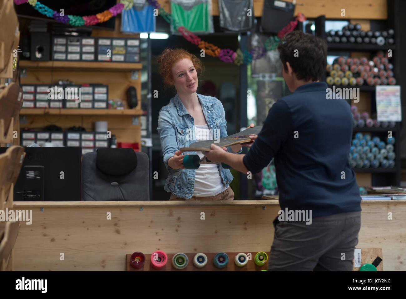 Woman working in skateboard shop, handing skateboard to customer - Stock Image