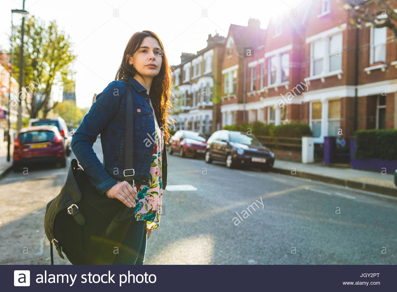Young woman standing in road, looking down street - Stock Image