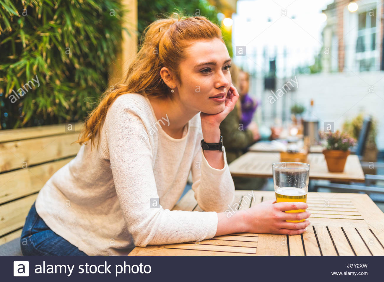 Woman sitting in pub garden, holding pint of beer, bored expression - Stock Image
