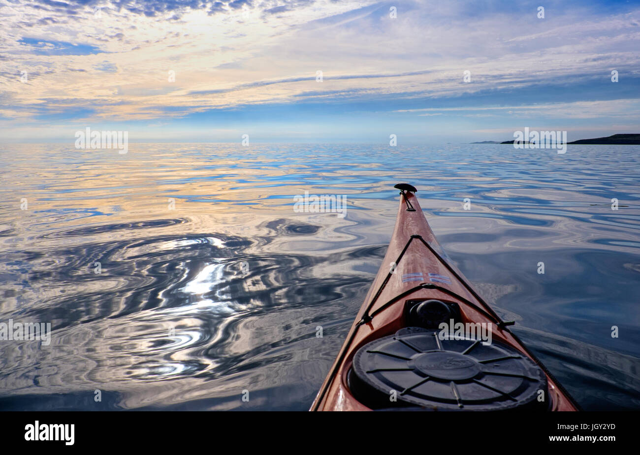 A sea kayak heading out into a calm, empty sea, Anglesey, Wales , UK - Stock Image