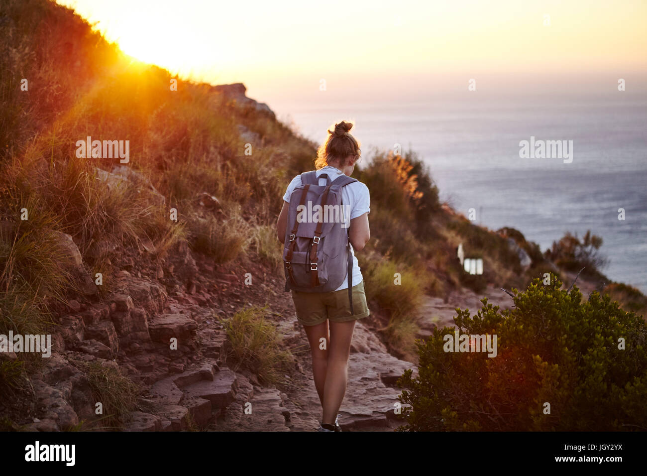 Young woman hiking, rear view, Lions head Mountain, Western Cape, Cape Town, South Africa - Stock Image