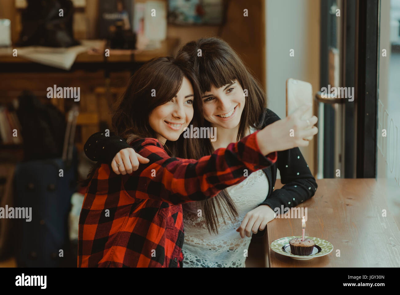 Two female friends, sitting in cafe, taking selfie, using smartphone, cupcake with candle on counter - Stock Image