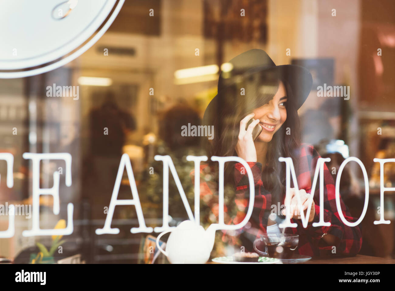 Young woman sitting in cafe, using smartphone, view through window - Stock Image