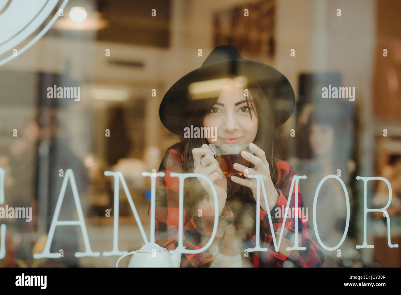 Portrait of young woman sitting in cafe, view through window - Stock Image