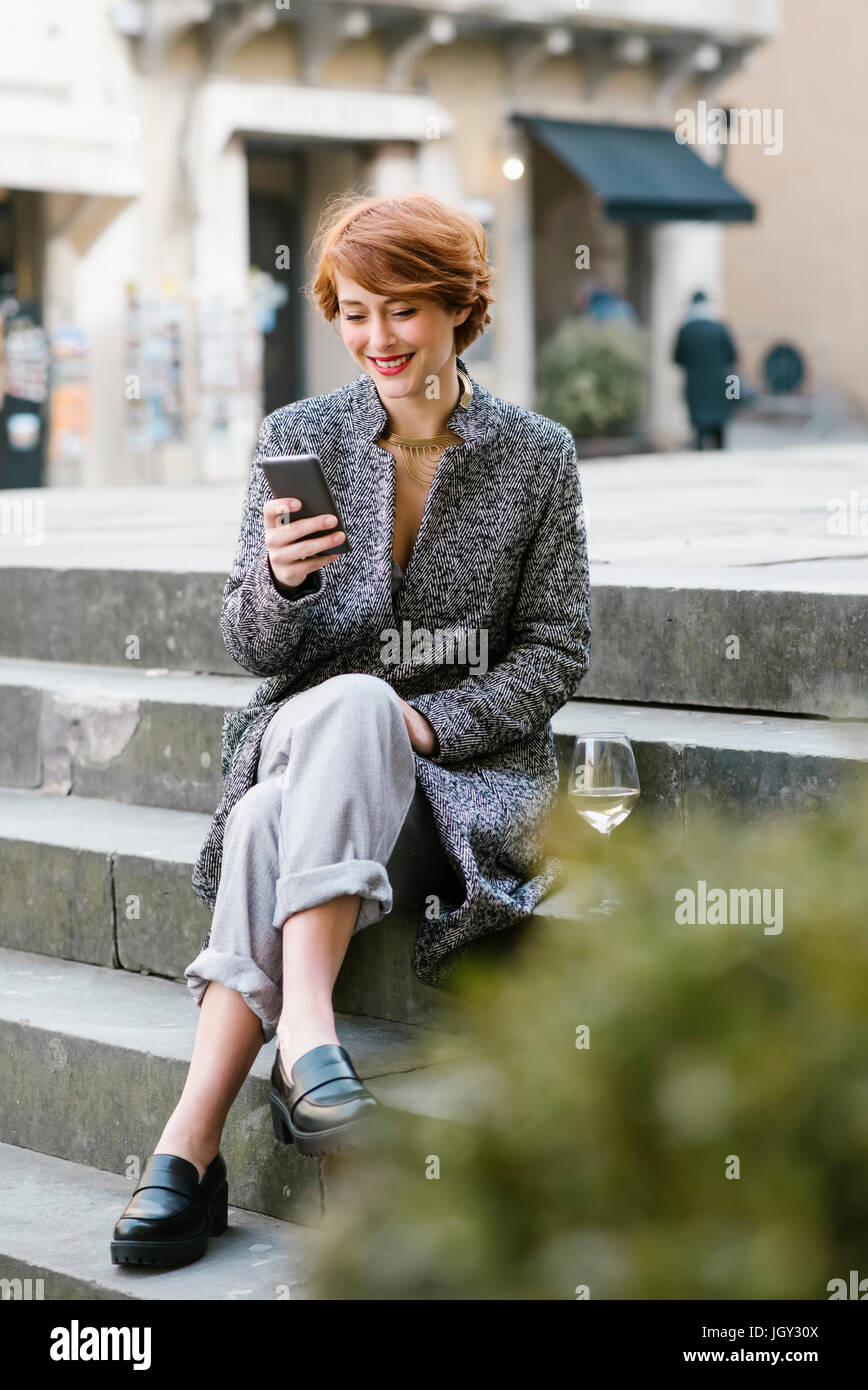 Young woman sitting on steps, using smartphone, glass of wine beside her - Stock Image