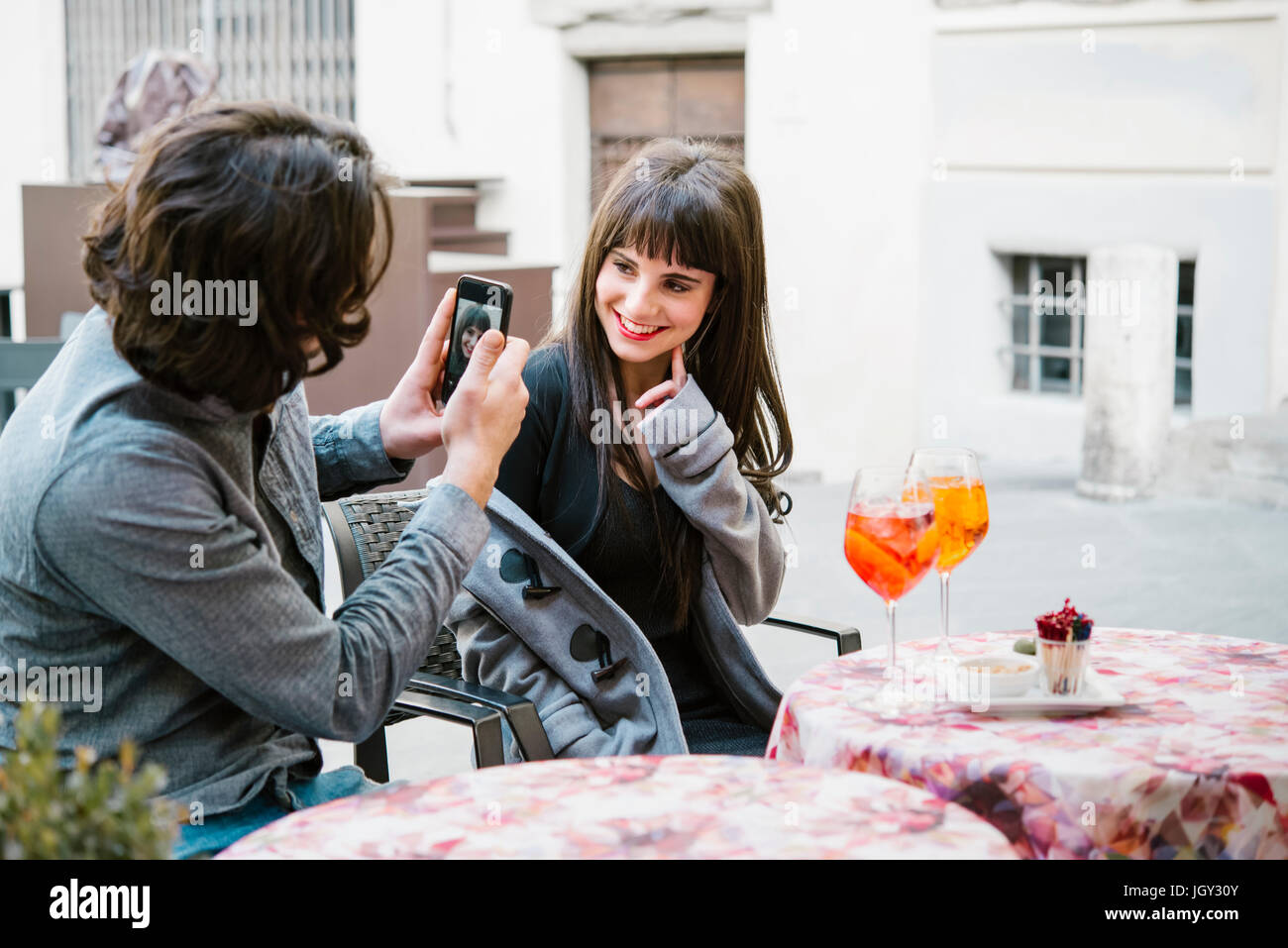 Young couple sitting outside cafe, man photographing woman, using smartphone - Stock Image