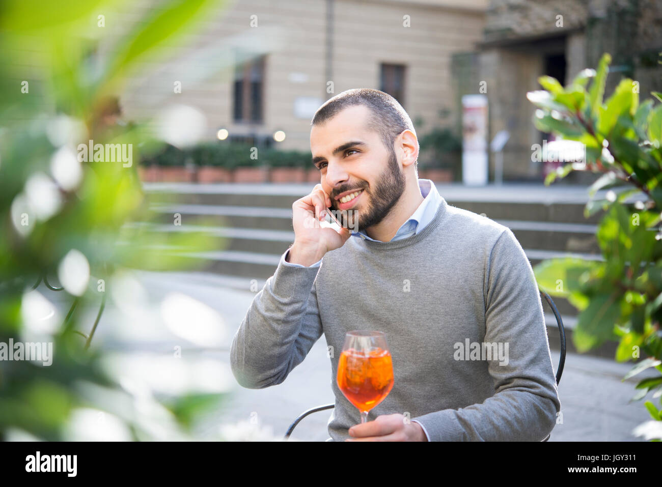 Young man sitting outside bar, holding drink, using smartphone - Stock Image