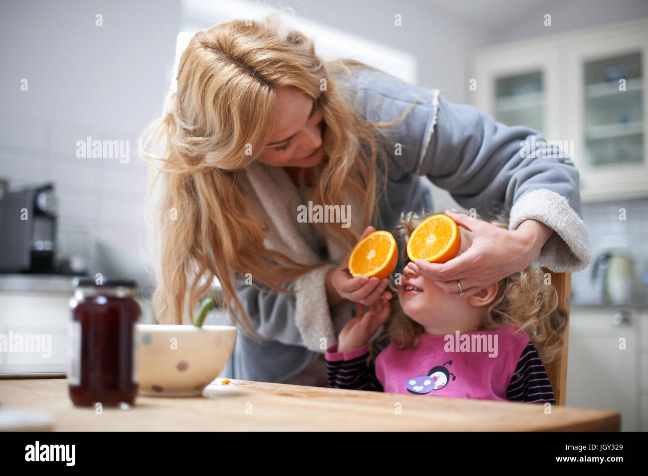 Young girl sitting at kitchen table, mother holding halved orange in front of daughter's eyes - Stock Image