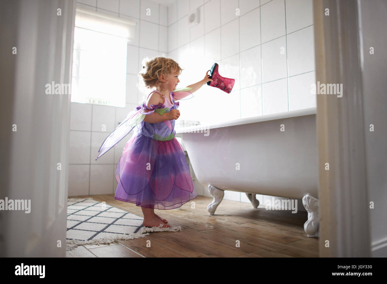 Young girl dressed in fairy costume, holding rubber boot over bathtub Stock Photo