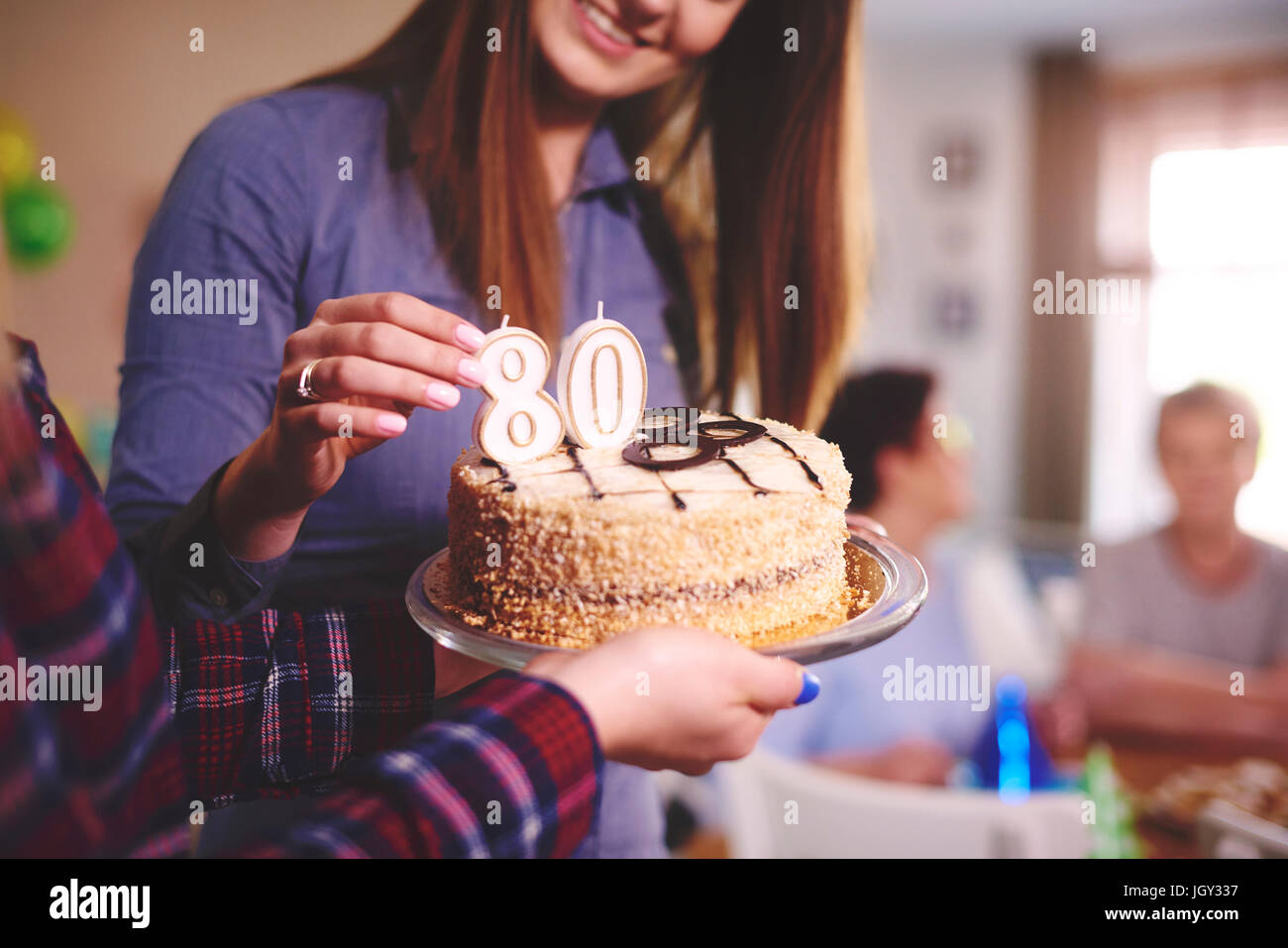 Daughter preparing birthday cake for mother at birthday party - Stock Image
