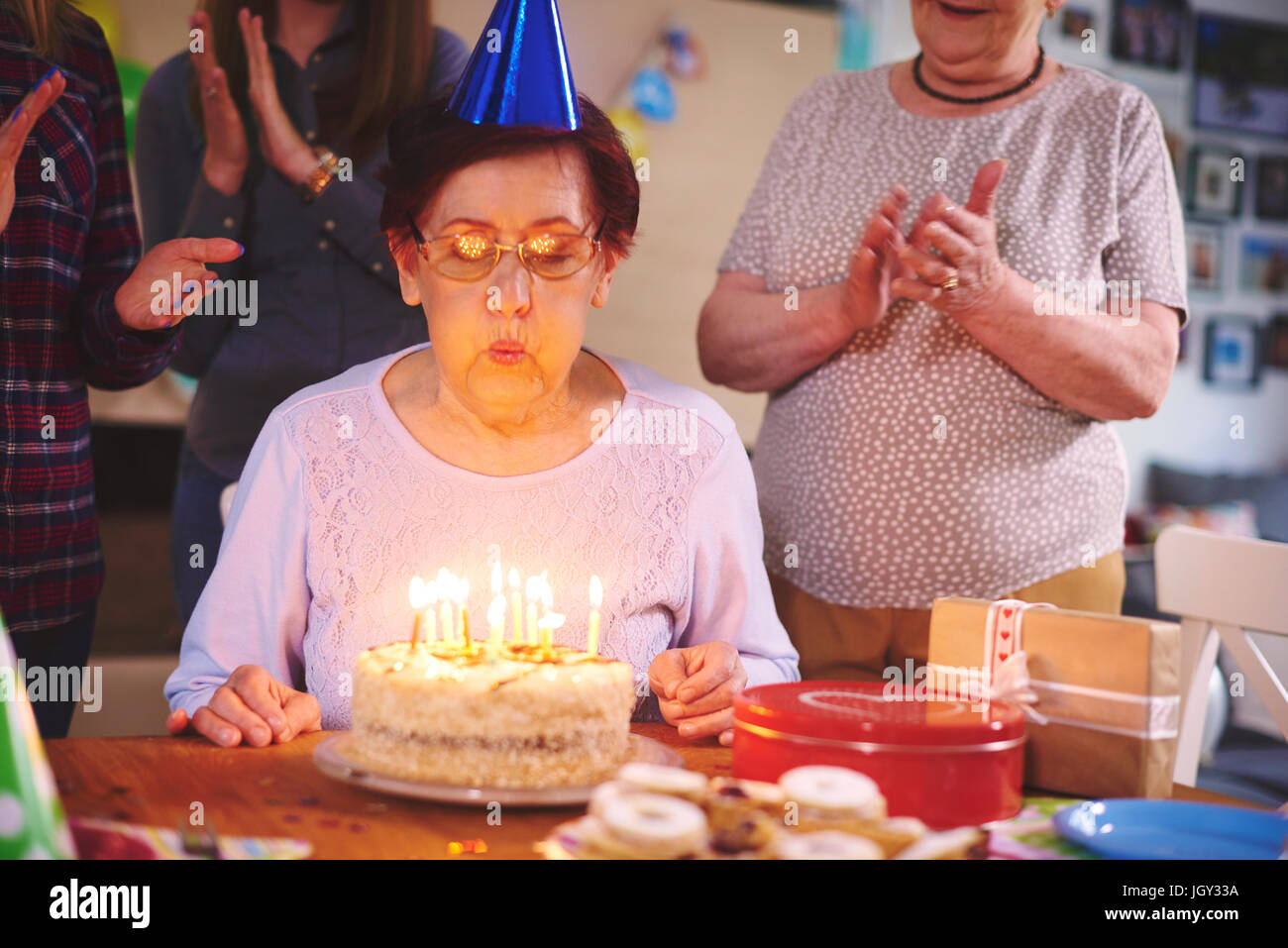 Senior woman blowing out candles on birthday cake at party - Stock Image