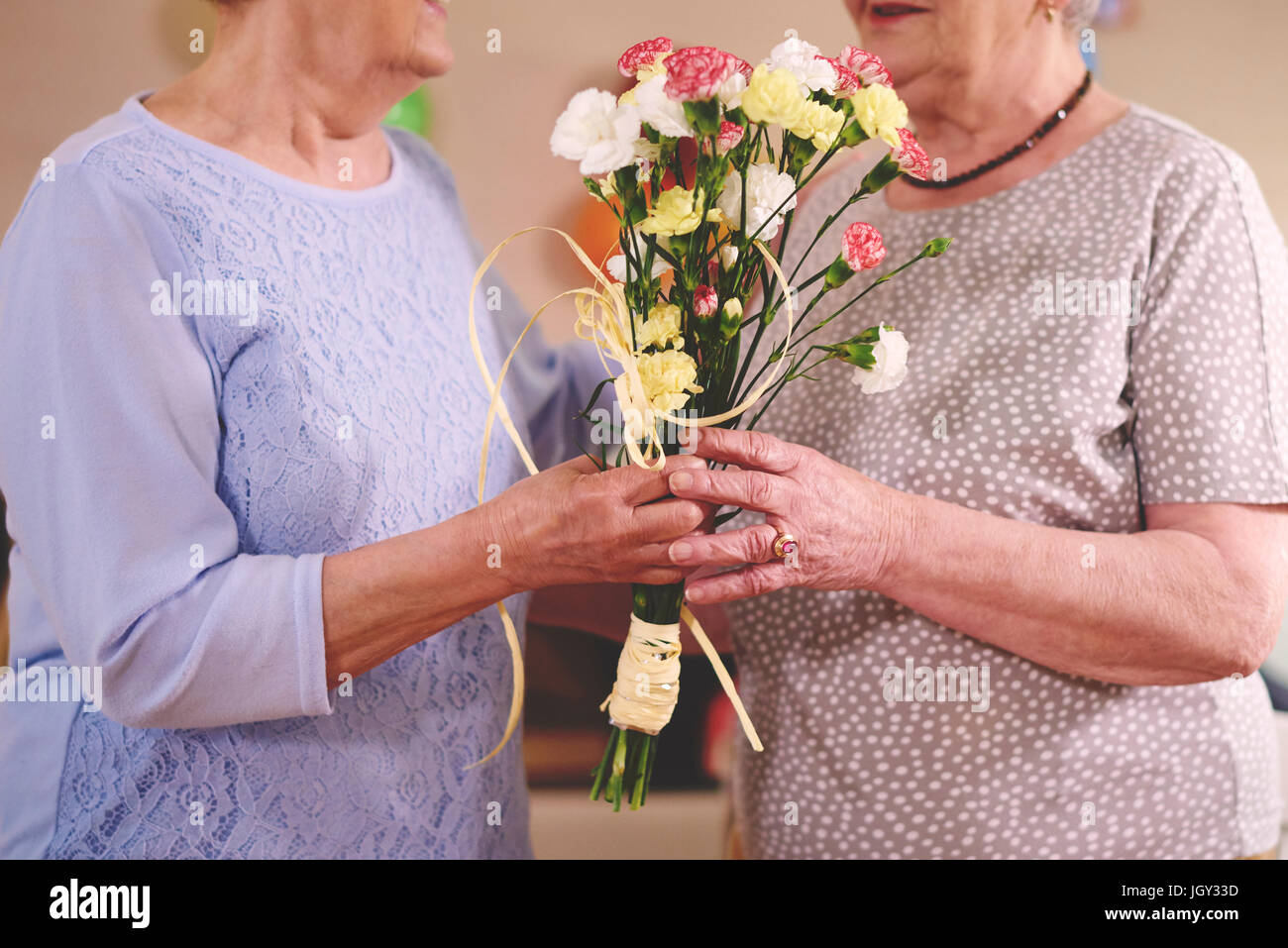 Senior woman giving flowers to friend at birthday party - Stock Image