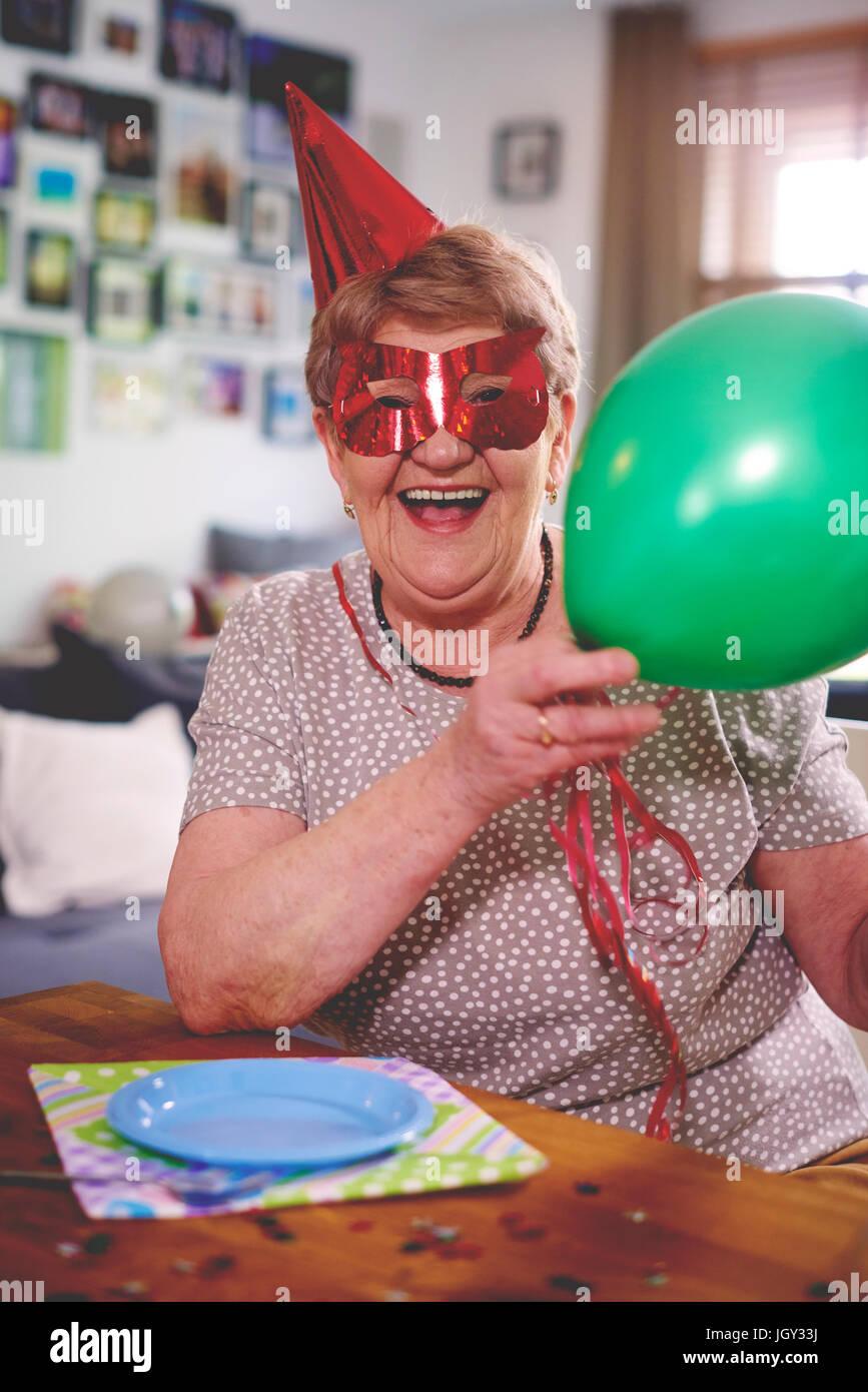 Senior woman waving balloons at birthday party - Stock Image