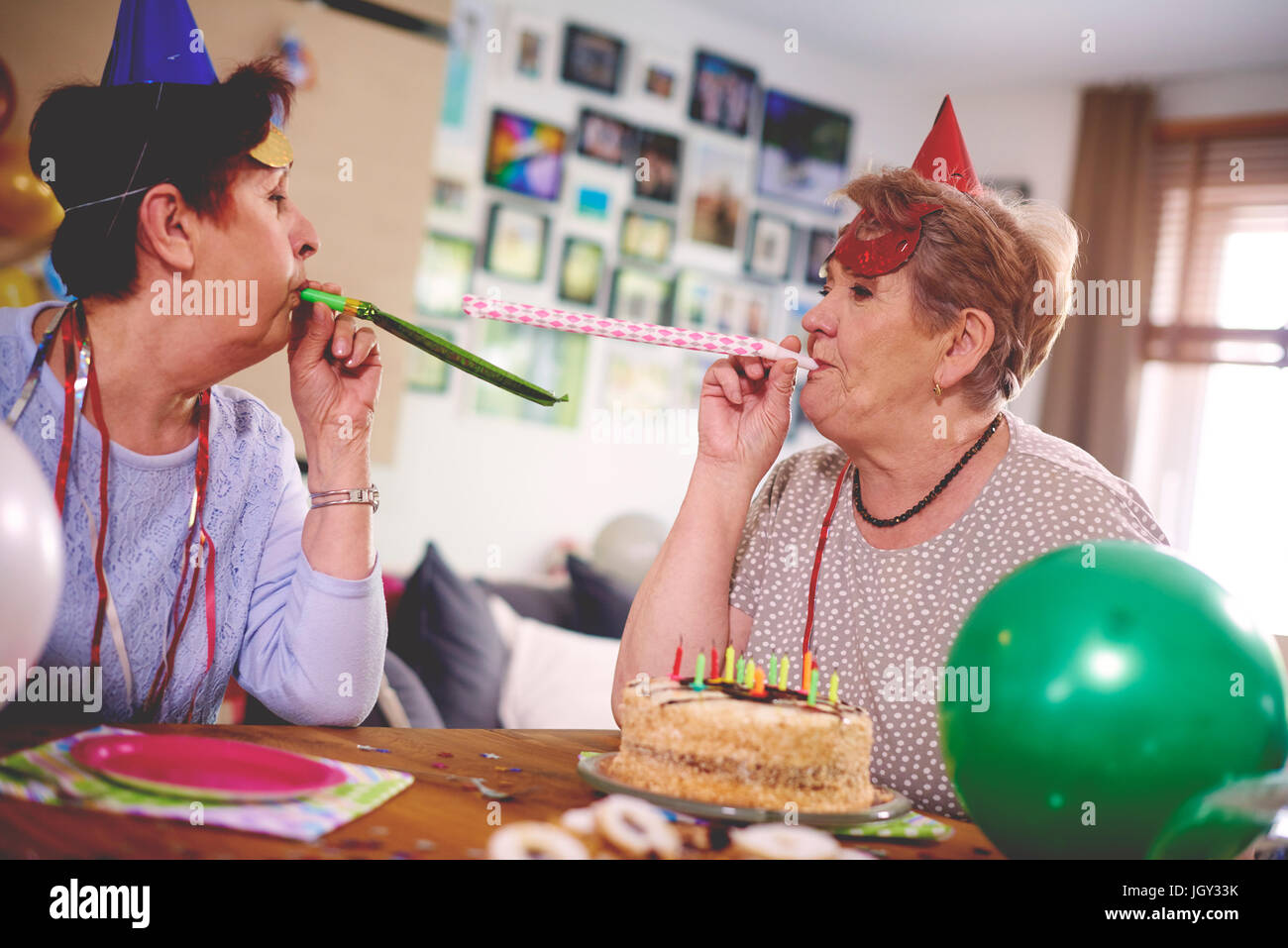 Senior women blowing party favor at each other - Stock Image