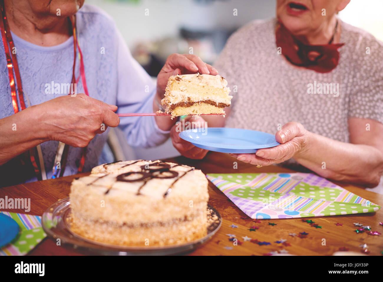 Senior women serving birthday cake at party - Stock Image