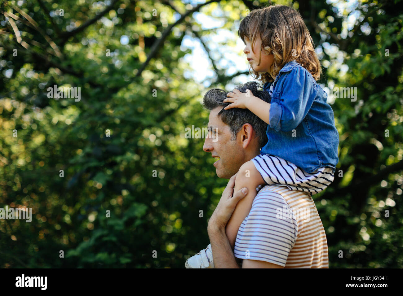 Father piggybacking little girl on nature walk - Stock Image