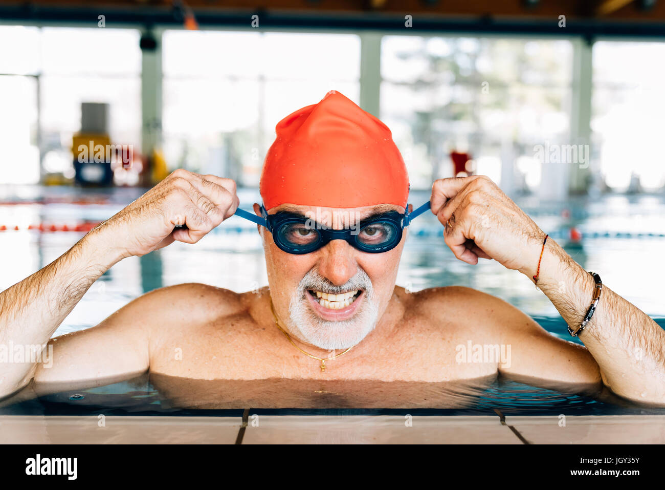 Senior man pulling mean face wearing goggles in swimming pool - Stock Image