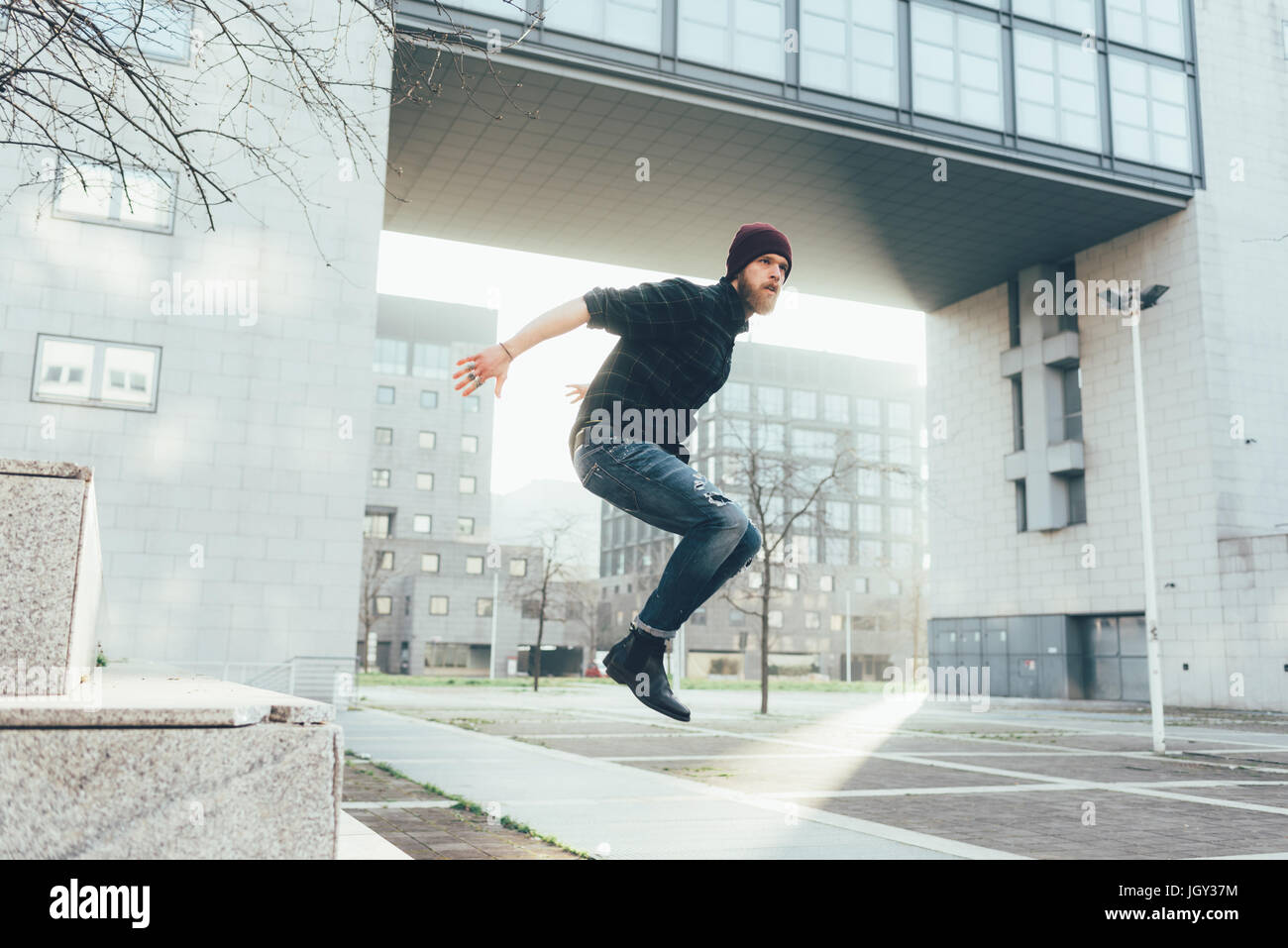 Young male hipster jumping mid air practicing parkour in city - Stock Image