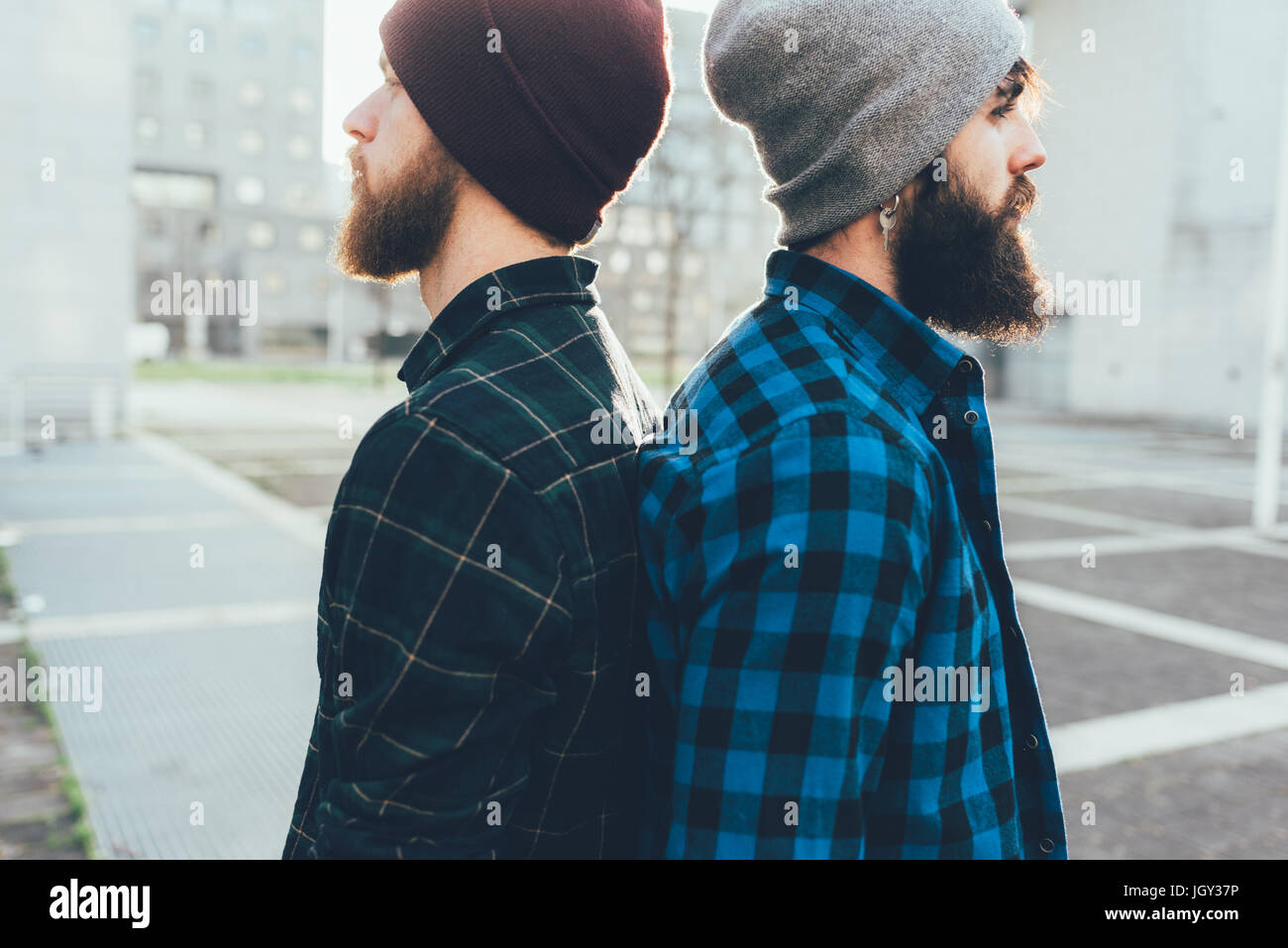 Portrait of two young male hipsters in knit hats back to back in city - Stock Image