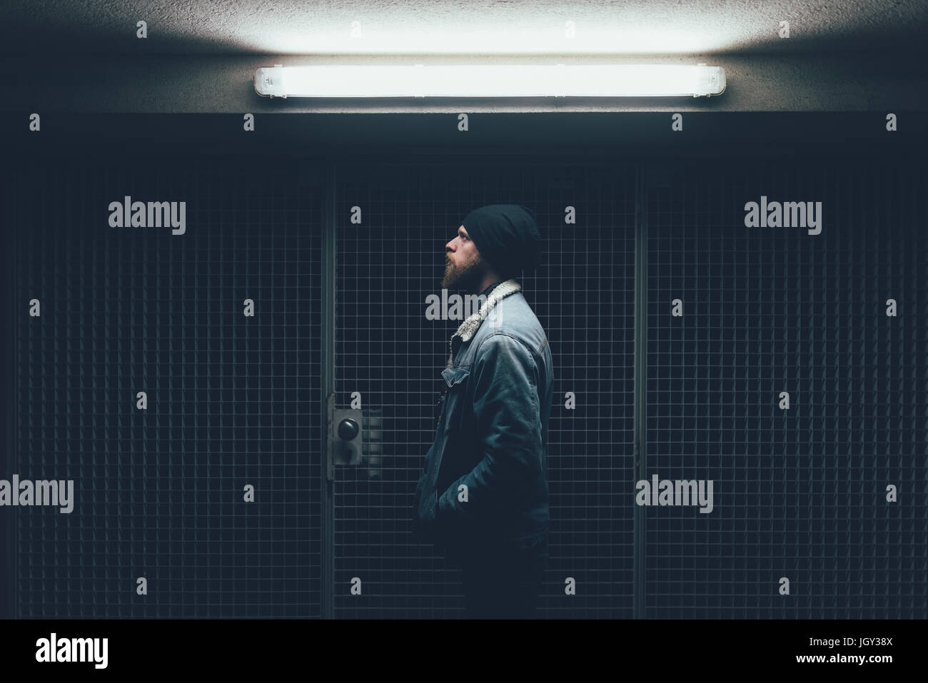 Young male hipster in dark city doorway at night - Stock Image