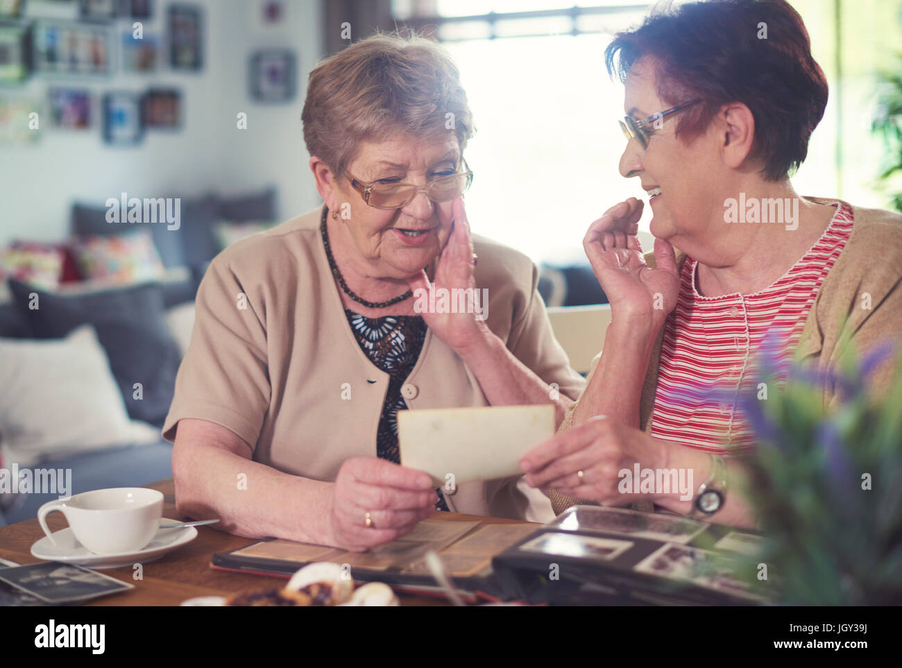 Two senior women chatting while looking at old photographs at table - Stock Image